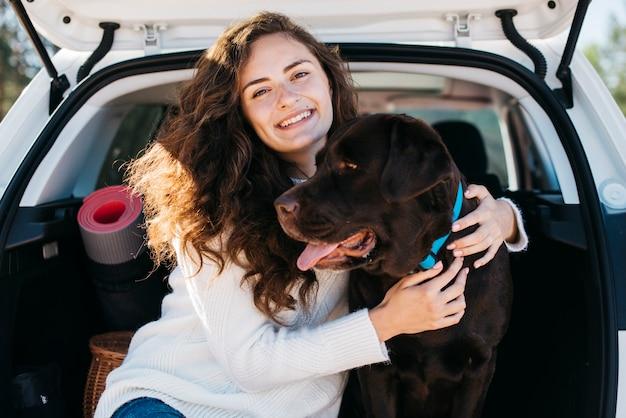 Frau, die mit ihrem hund im offenen stamm sitzt Kostenlose Fotos