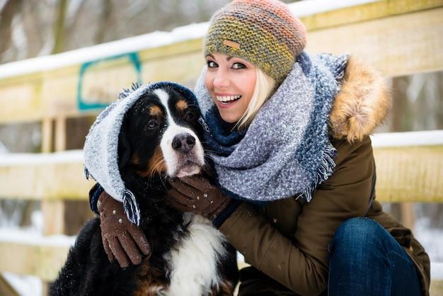 Frau, die mit ihrem hund im schnee spielt Premium Fotos