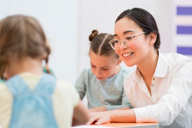 Frau, die mit ihren schülern während des unterrichts spricht Kostenlose Fotos