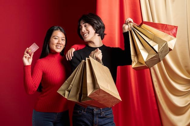 Frau, die mit kreditkarte und mann für chinesisches neues jahr aufwirft Kostenlose Fotos