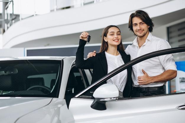 Frau, die mit männlicher seles person in einem autosalon spricht Kostenlose Fotos
