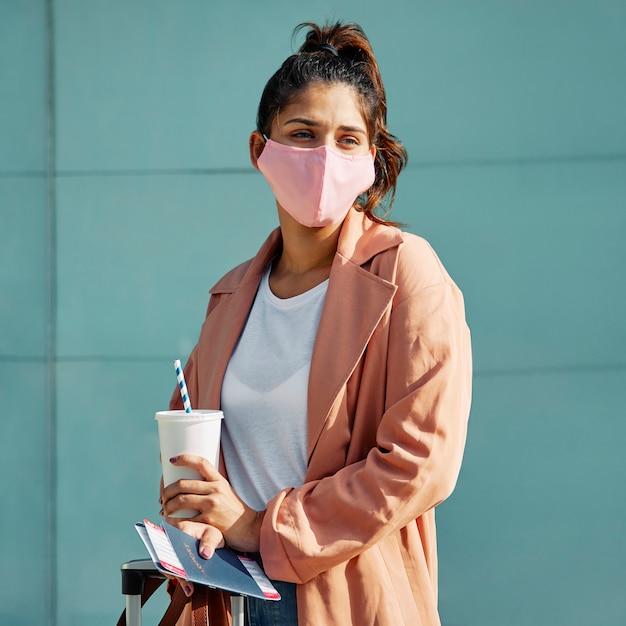 Frau, die mit medizinischer maske und pass am flughafen während der pandemie aufwirft Kostenlose Fotos