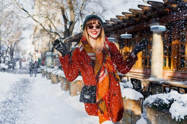 Frau, die mit schnee spielt, spaß hat und feiertage genießt Kostenlose Fotos