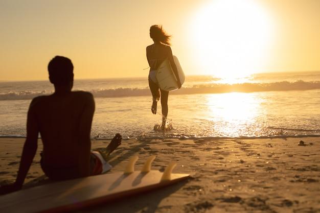 Frau, die mit surfbrett während mann sich entspannt auf dem strand während des sonnenuntergangs läuft Kostenlose Fotos
