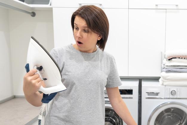 Frau, die mit überraschung unten des defekten eisens in der waschküche mit waschmaschine schaut Premium Fotos