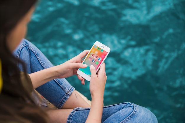 Frau, die mobiltelefon mit social media-benachrichtigungen auf schirm verwendet Kostenlose Fotos