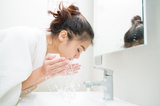 Frau, die morgens ihr gesicht vor dusche säubert Premium Fotos