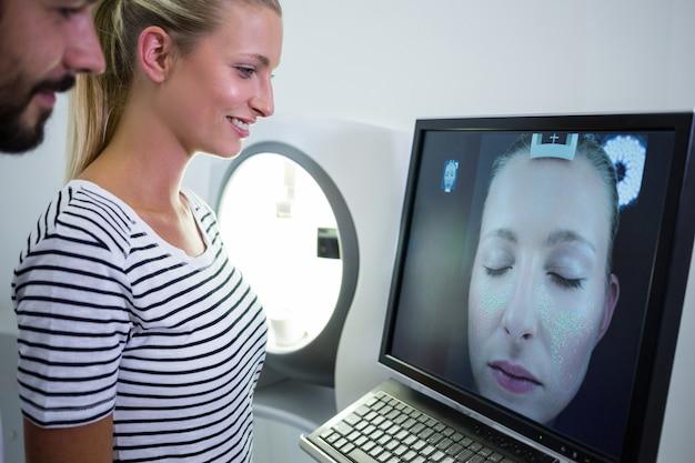 Frau, die mri scan-bericht auf computerbildschirm sucht Kostenlose Fotos