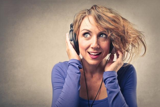 Frau, die musik auf kopfhörern hört Premium Fotos