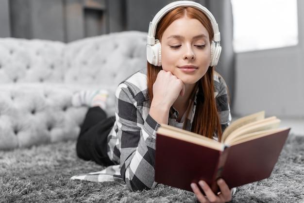 Frau, die musik hört und liest Kostenlose Fotos