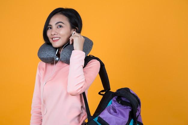 Frau, die musik mit nackenkissen und schultasche hört Premium Fotos