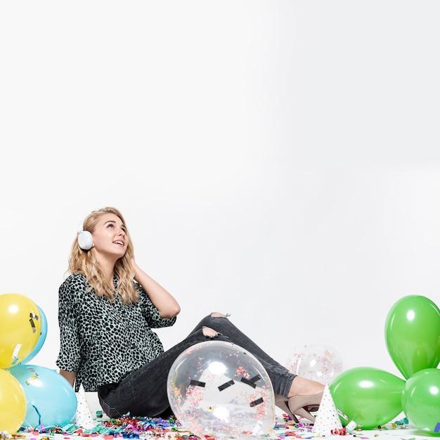 Frau, die musik umgeben durch ballone hört Kostenlose Fotos