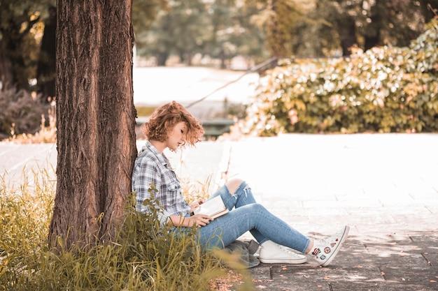 Frau, die nahe baum und lesebuch sitzt Kostenlose Fotos