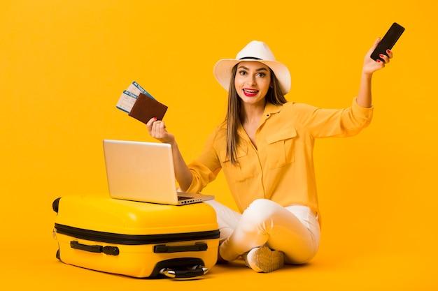 Frau, die nahe bei gepäck beim halten des smartphone und der flugtickets aufwirft Kostenlose Fotos