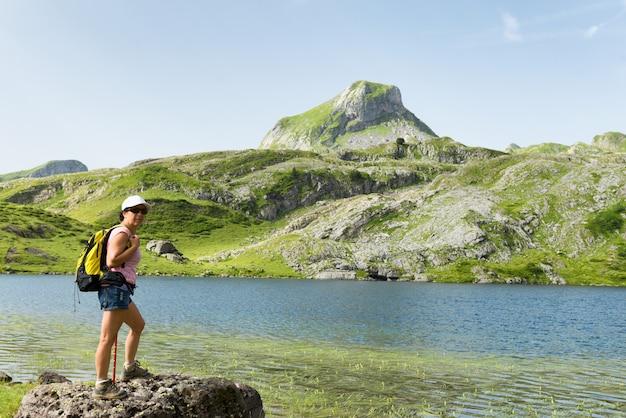 Frau, die nahe einem gebirgssee wandert Premium Fotos