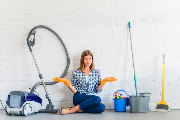 Frau, die nahe reinigungsausrüstungen vor backsteinmauer sitzt Kostenlose Fotos
