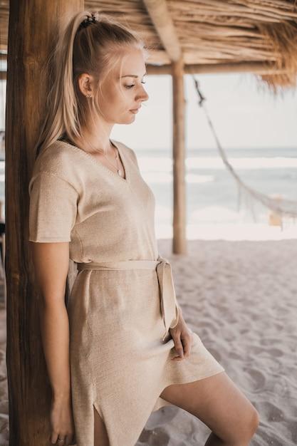 Frau, die neben einer hölzernen säule auf sand steht Kostenlose Fotos
