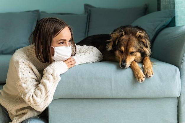 Frau, die neben ihrem hund zu hause während der pandemie sitzt Kostenlose Fotos