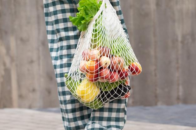 Frau, die obst und gemüse mit wiederverwendbarer baumwolle eco-erzeugnistasche geht und kauft. zero waste lifestyle-konzept Premium Fotos