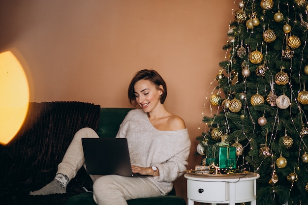 Frau, die online auf weihnachtsgeschäft kauft Kostenlose Fotos