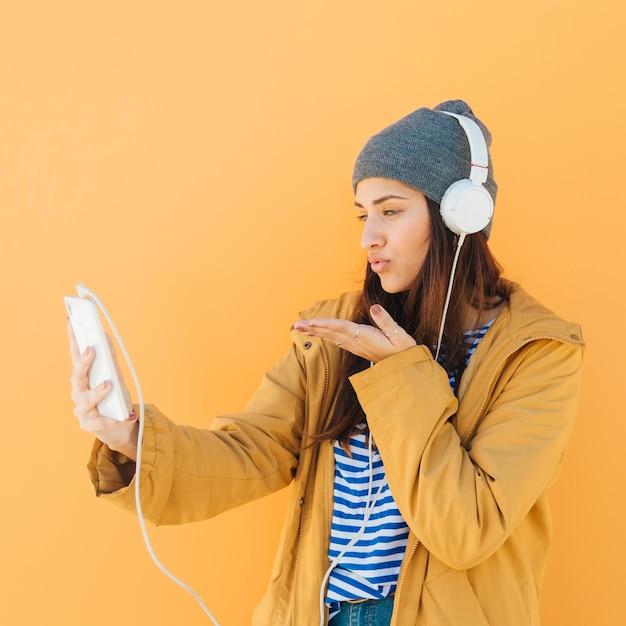 Frau, die online einen kuss während eines videoanrufs mit einem intelligenten telefon sendet Kostenlose Fotos