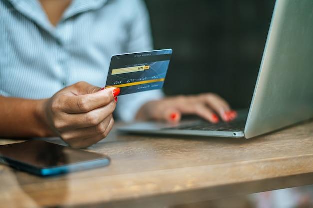 Frau, die online mit einer kreditkarte zahlt Kostenlose Fotos