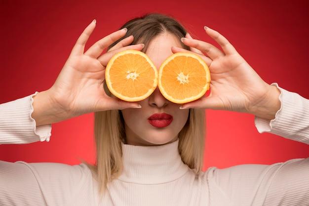 Frau, die orange scheiben über ihren augen hält Kostenlose Fotos