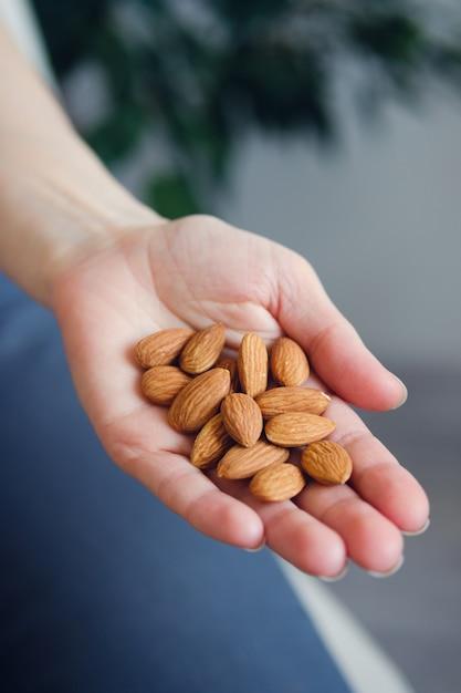 Frau, die organische mandelnüsse in den händen, nahaufnahme hält Premium Fotos