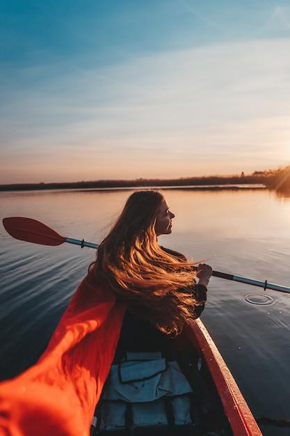 Frau, die paddel in einem kajak auf dem fluss hält Kostenlose Fotos