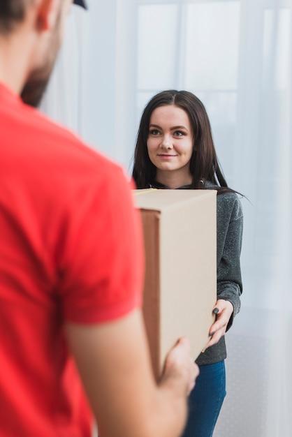 Frau, die paket mit kurier empfängt Kostenlose Fotos