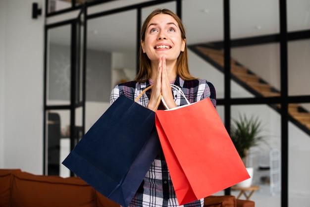 Frau, die papiertüten hält und betet Kostenlose Fotos