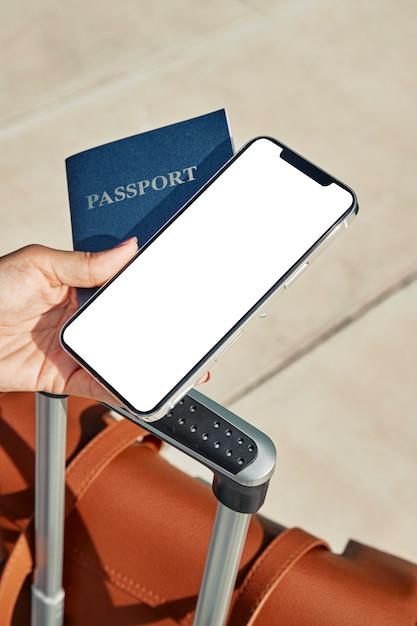 Frau, die pass und smartphone mit gepäck am flughafen während der pandemie hält Kostenlose Fotos