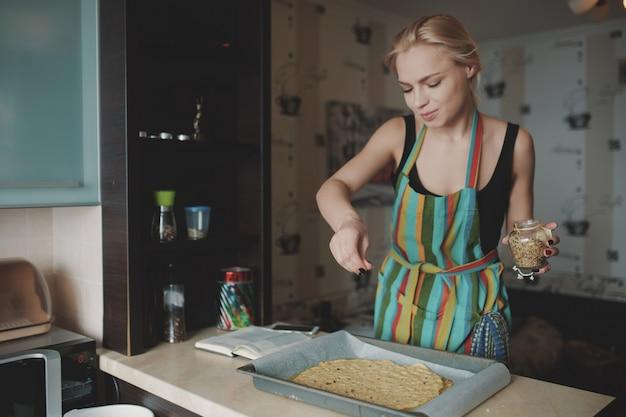Frau, die pizza an der küche kocht Kostenlose Fotos
