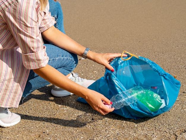 Frau, die plastikflasche in der tasche sammelt Kostenlose Fotos