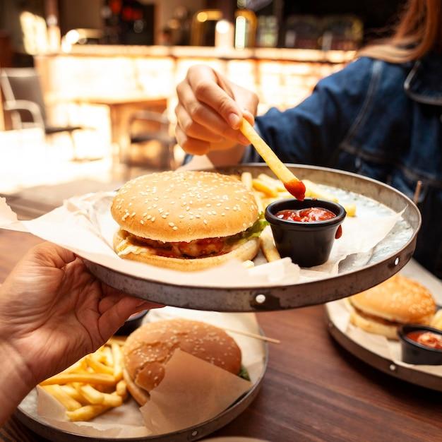 Frau, die pommes frites mit ketchup isst Kostenlose Fotos