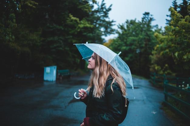 frau die regenschirm hält während sie in der mitte der