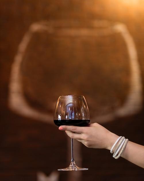 Frau, die rotweinglas mit glasform hält Premium Fotos