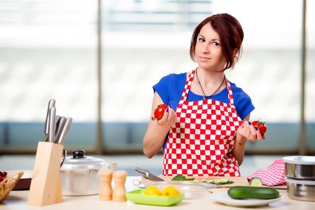 Frau, die salat in der küche zubereitet Premium Fotos