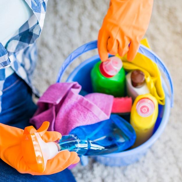 Frau, die sauberere sprühflasche vom blauen eimer entfernt Kostenlose Fotos