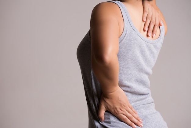 Frau, die schmerz in verletztem rücken hat. gesundheitswesen und rückenschmerzen konzept. Premium Fotos