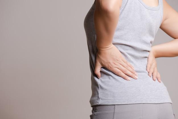 Frau, die schmerz in zurück verletzt hat. gesundheitswesen und rückenschmerzen konzept. Premium Fotos