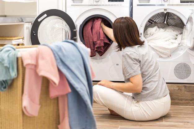 Frau, die schmutzige kleidung in der waschmaschine für das waschen im modernen gebrauchsraum lädt Premium Fotos