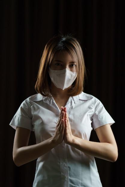 Frau, die schutzbrille und maske trägt. begrüßung mit