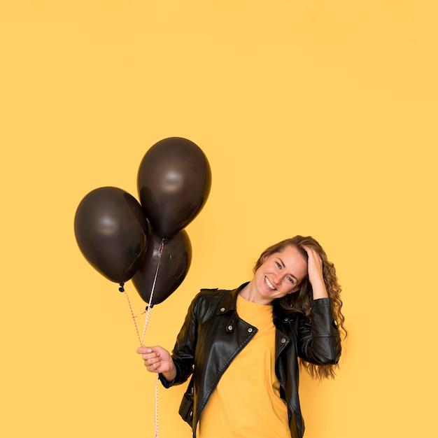 Frau, die schwarze luftballons vorderansicht hält Kostenlose Fotos