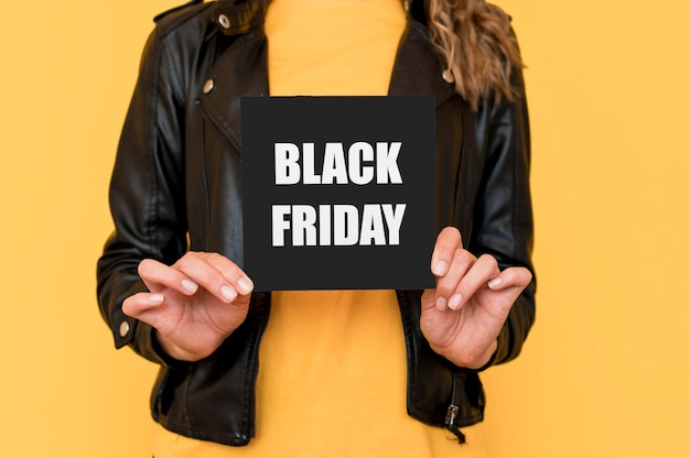 Frau, die schwarzes freitagsetikett hält Kostenlose Fotos