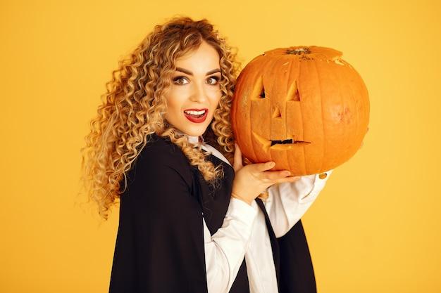 Frau, die schwarzes kostüm trägt. dame mit halloween make-up. mädchen, das auf einem gelben hintergrund steht. Kostenlose Fotos