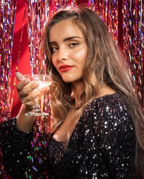 Frau, die seitlich ein glas champagner hält Kostenlose Fotos