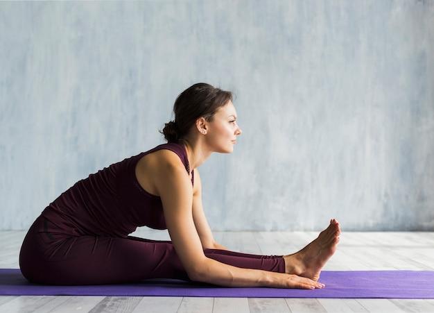 Frau, die sich vorwärts beim üben von yoga lehnt Kostenlose Fotos