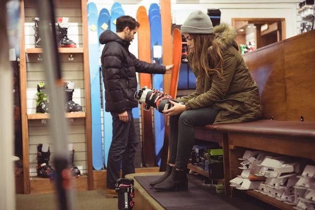 Frau, die skischuh in einem geschäft auswählt Kostenlose Fotos