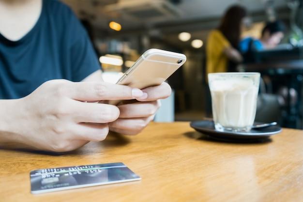 Frau, die smartphone für bewegliche transaktion verwendet oder online kauft Premium Fotos